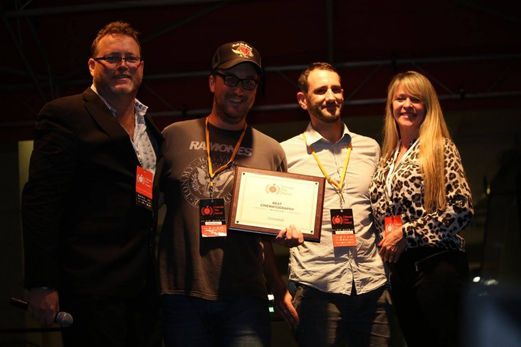 """""""Concealed"""" director and producer Shane T. Hall (2nd left) and producer Lyall Sumner receive the Best Cinematography award at the OFFX Award Ceremony Saturday. Photo: J. Willie David III/Florida National News."""