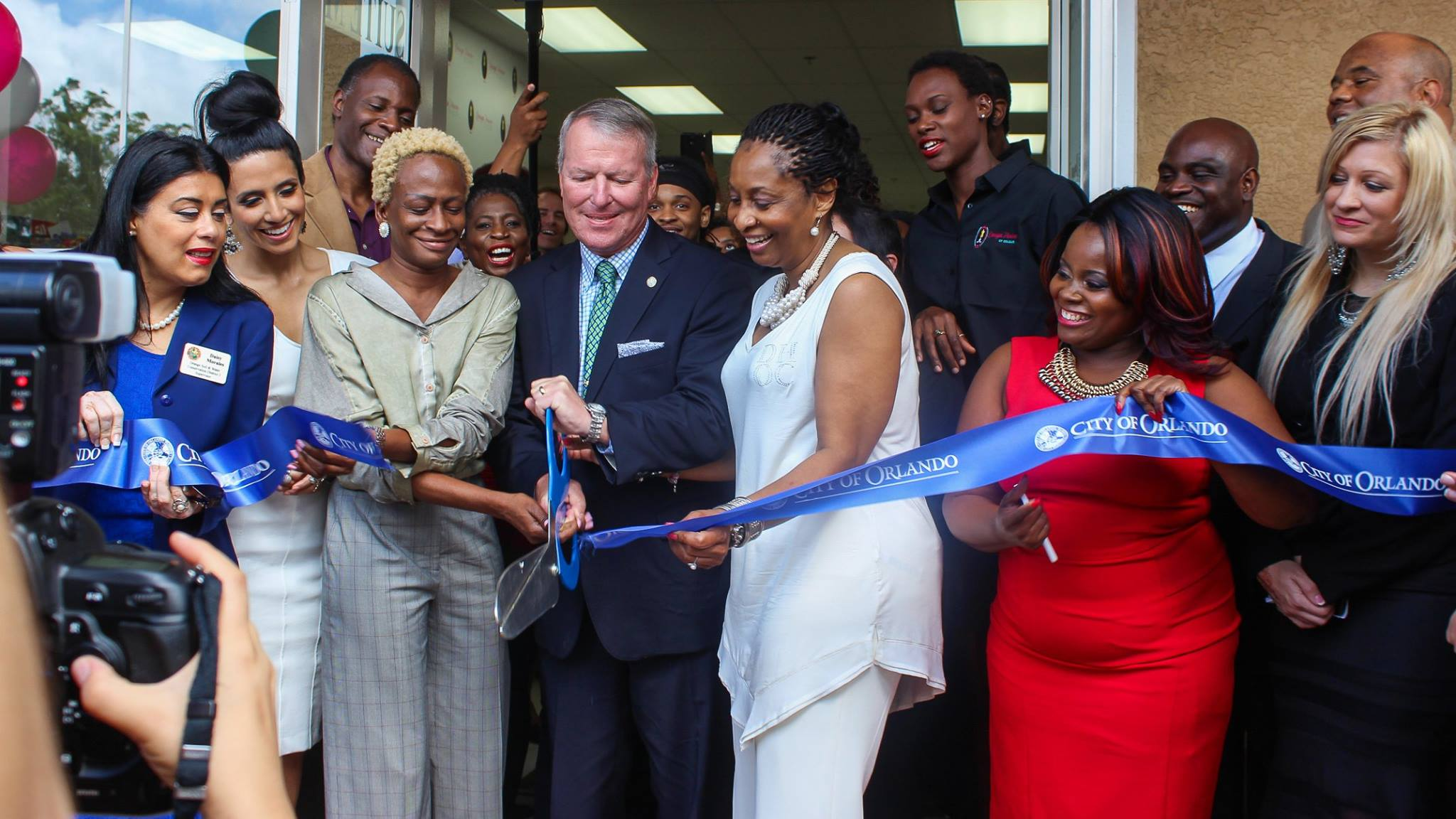 Design House of Colour owner Dr. Renee Forbes-Williams (center, in off-white) officially cuts the opening ribbon with Orlando Mayor Buddy Dyer, District 5 Commissioner Regina Hill (left of Mayor Dyer), and District 2 Soil & Water Conservation Supervisor Daisy Morales (left, in blue). Photo: J. Willie David III/Florida National News.