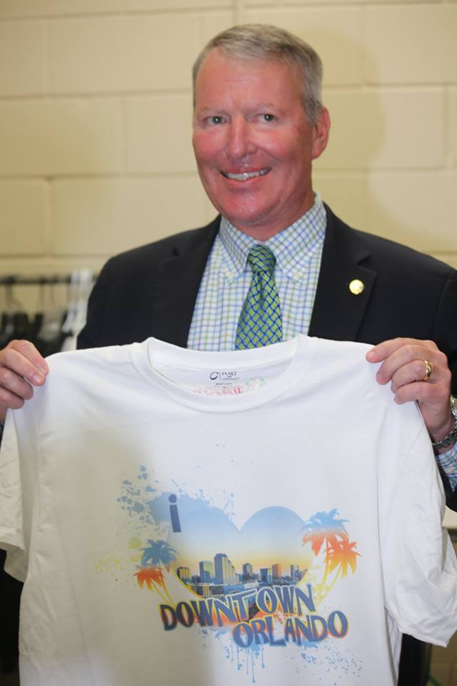 "Orlando Mayor Buddy Dyer receives his custom ""I Love Orlando"" t-shirt, printed on the spot during Design House of Colour's grand opening Thursday. Photo: J. Willie David III/Florida National News."