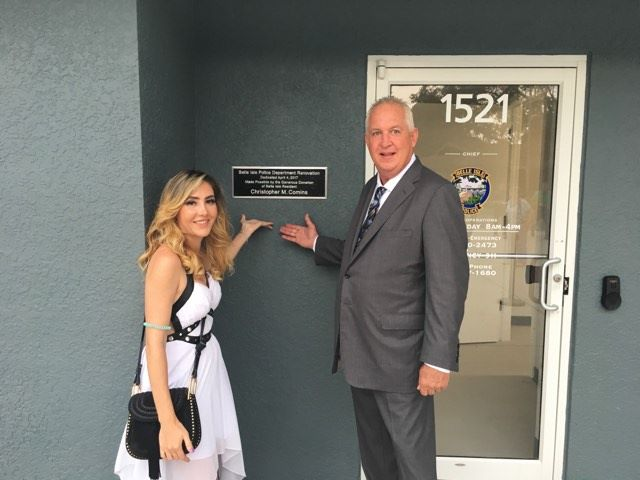 Ashley Morgan (left) points with Chris Comins to a personalized plaque recognizing Comins's generous contribution to the Belle Isle Police Department's renovation. Photo: Randy Ross/Florida National News.