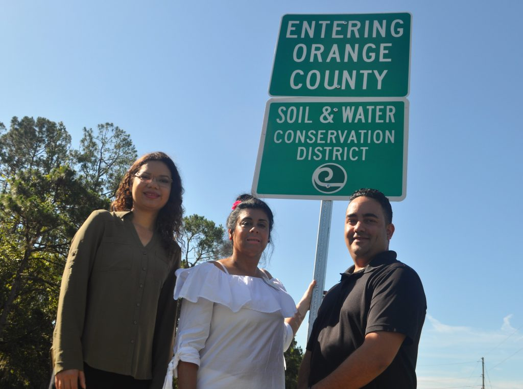 (l-r) Orange County District 5 Commissioner Emily Bonilla, Orange Soil & Water Conservation District 2 Supervisor and Board Vice Chairman Daisy Morales along with USDA Natural Resources Conservation Service Conservationist Marcos Loperena unveiled two new signs at the Seminole County-Orange County border Thursday morning, June 14, 2018. Photo by Willie David / Florida National News