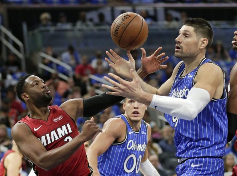 Orlando Magic's Nikola Vucevic (right) and Miami Heat's Dwayne Wade (left) battle for the ball at Amway Center Wednesday night. Photo: AP.