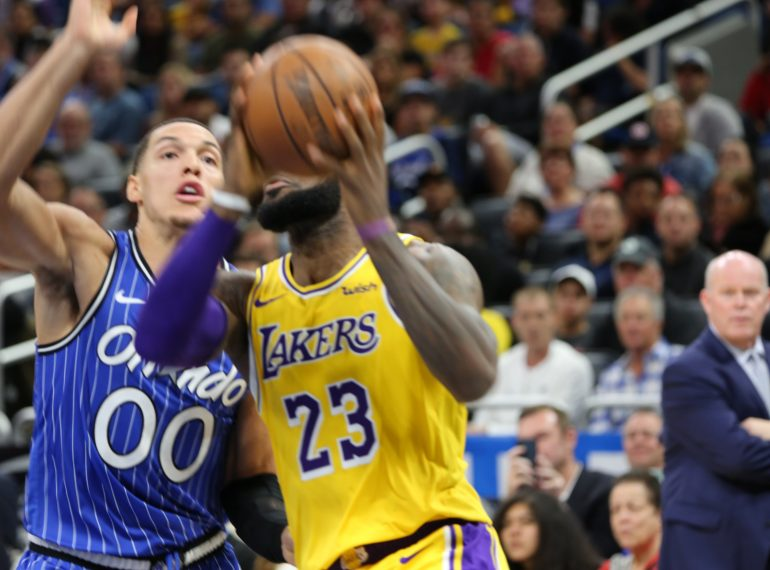 L.A. Lakers' Lebron James (#23) drives to the net with Orlando Magic's Aaron Gordon (#00), along with three other Magic players (not seen in this photo) on the defense. Photo: Willie David/Florida National News.