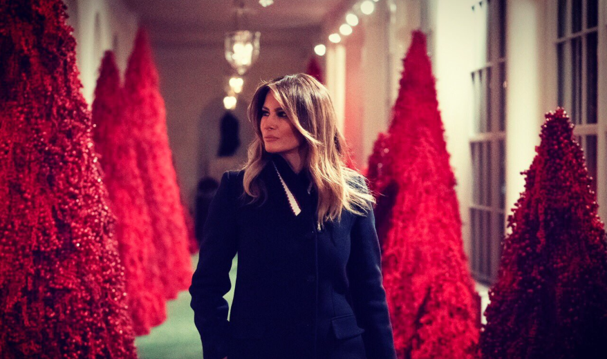 First Lady Melania Trump walks among the now controversial red Christmas trees in the White House. Photo: @FLOTUS/Twitter
