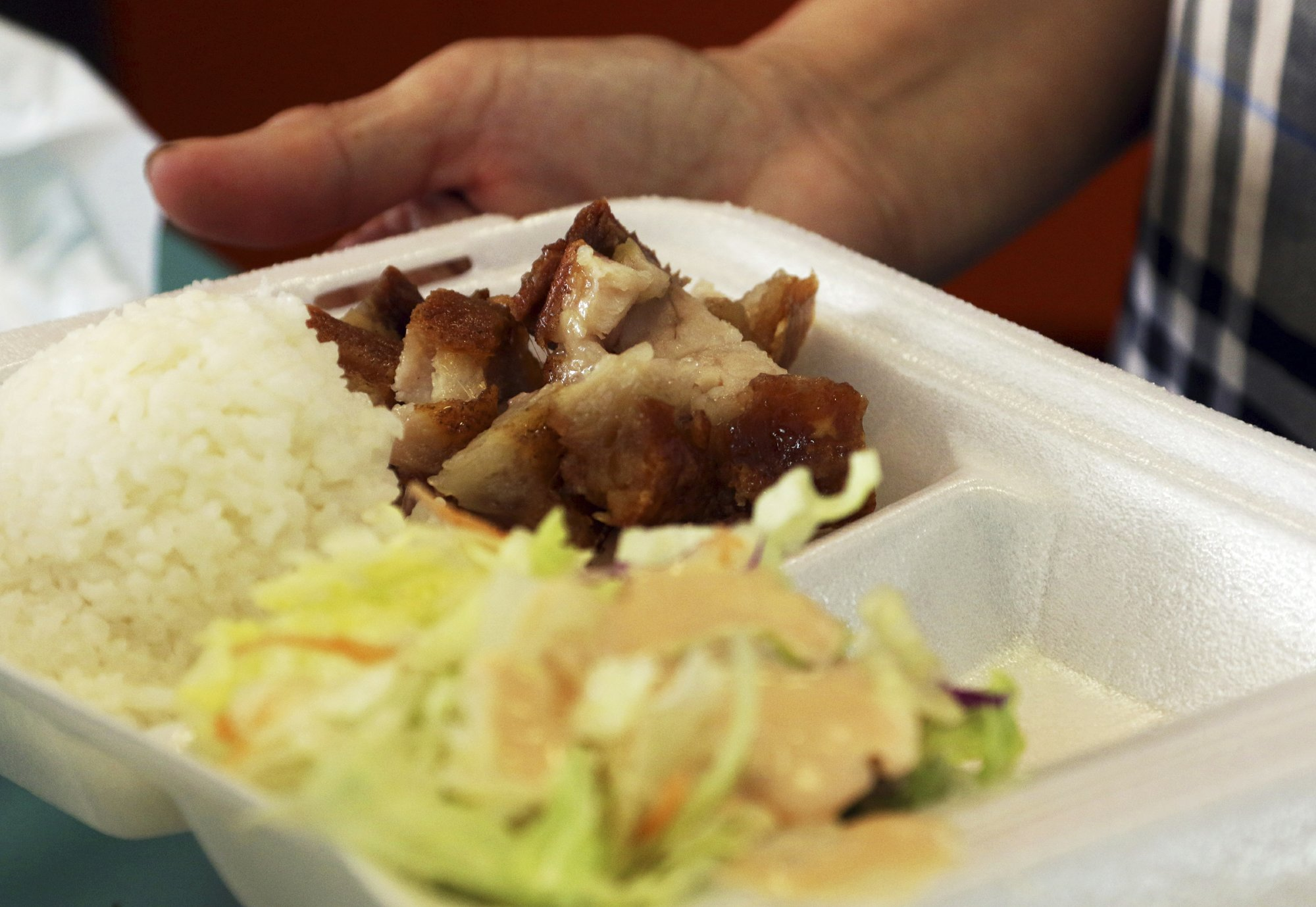 In this Thursday, March 14, 2019 photo, Belinda Lau, manager of the Wiki Wiki Drive Inn takeout restaurant in Honolulu, holds a polystyrene foam box containing an order of roast pork, rice and salad. Hawaii would be the first state in the nation to ban most plastics used at restaurants, including polystyrene foam containers, if legislation lawmakers are considering is enacted. The aim is to cut down on waste that pollutes the ocean. (AP Photo/Audrey McAvoy)