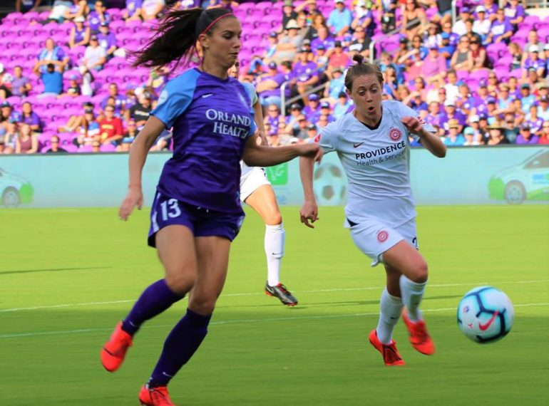 Portland Thorns defender Meghan Klingenberg (in white) duels with Orlando Pride forward Alex Morgan for the ball during the NWSL season opening match at Orlando City Stadium Sunday, April 14, 2019. Photo: Willie David/Florida National News.