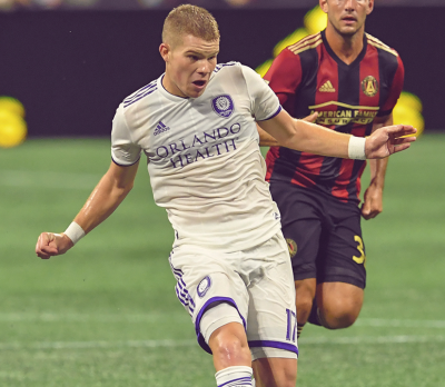 Orlando City's Chris Mueller (in white) battle for the ball against Atlanta United at Mercedes-Benz Stadium. Photo courtesy of The Bleacher Report.