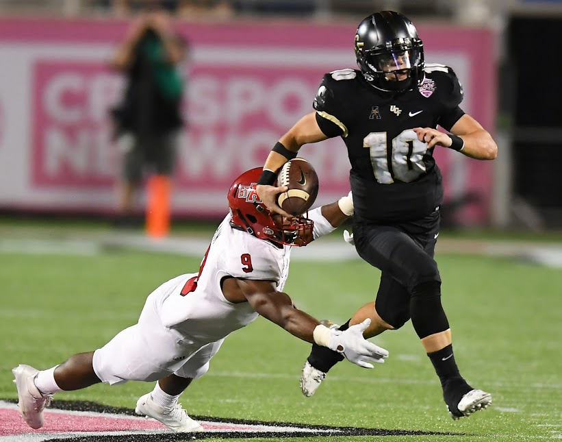 UCF Knights quarterback McKenzie Milton (#10) dodges a tackle as he rushes the ball during the 2016 AutoNation Cure Bowl. Photo: Orlando Sports Foundation.