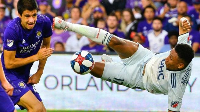 New England Revolution forward Juan Agudelo (right) tries for the ball against Orlando City defender Joao Moutinho during their US Open Cup match at Exploria Stadium Wednesday, June 19, 2019. Photo: USA TODAY Sports.