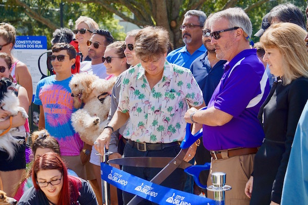 Orlando Mayor Buddy Dyer (center, with scissors) and Orlando Commissioner Patty Sheehan (left of Mayor, in white), along with other Orlando residents and dog lovers, cut the ribbon to re-open Constitution Green Park Thursday, August 15, 2019. Photo: Leyton Blackwell/Florida National News.