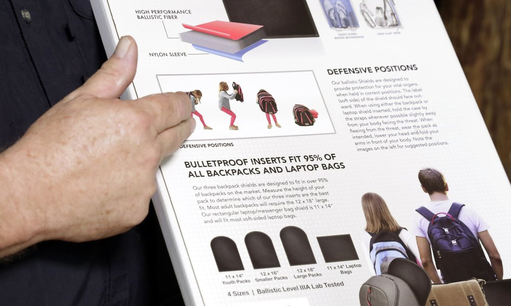 Steve Naremore, founder and CEO of TuffyPacks, notes the use and various options of his bulletproof inserts on the packaging of the product that can be placed into various makes and sizes of backpacks, during a demonstration at the Shiloh Shooting Range, Friday, August 9, 2019, in Houston. His company produces some bullet-resistant backpacks but the bulk of his business is in removable ballistic shields that are inserted in backpacks. (AP Photo/Michael Wyke)