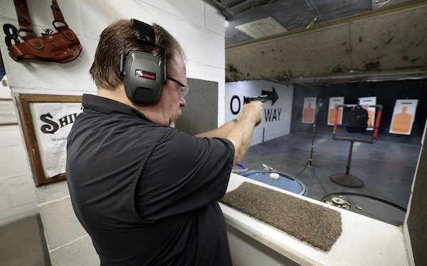 Steve Naremore, founder and CEO of TuffyPacks, fires nine rounds of 180 grain .40 S&W from his Glock handgun into a backpack seven yards away containing one of his ballistic shields, made of Aramid fiber ballistic material providing level IIIA handgun only protection, during a demonstration of the stopping ability of the product at the Shiloh Shooting Range, Friday, August 9, 2019, in Houston. His company produces some bullet-resistant backpacks but the bulk of his business is in removable ballistic shields that are inserted in backpacks. (AP Photo/Michael Wyke)