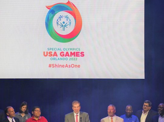 Orlando Mayor Buddy Dyer (right of center) and Orange County Mayor Jerry Demings (right) look on as Special Olympics 2022 USA Games President & CEO Joe Dzaluk (center) unveils the completed logo, comprised of the unified designs of nine Special Olympics Athletes. Photo: Willie David/Florida National News.
