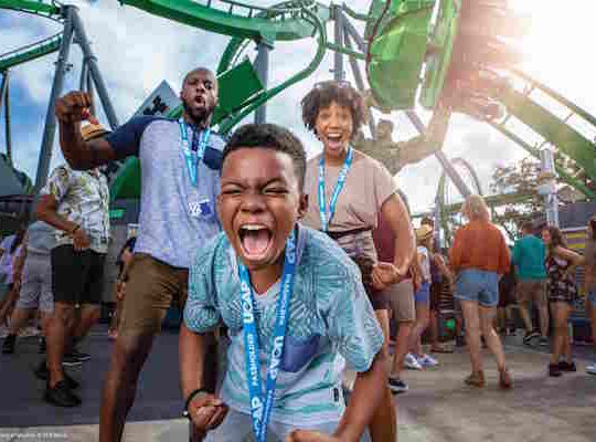 An African American family has fun flexing for the camera at Universal Orlando Resort.