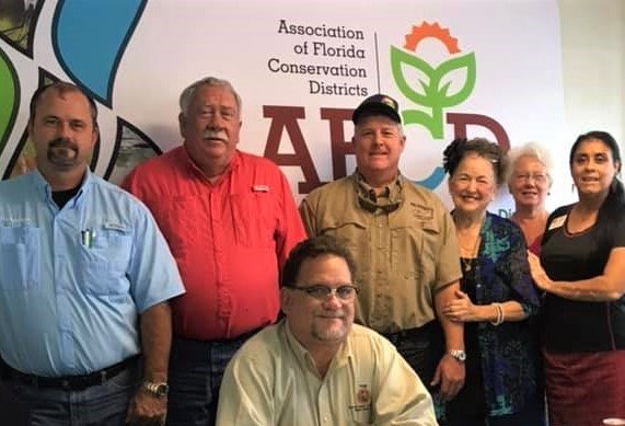 Associate of Florida Conservation Districts President Jeff Moore (rear, ball cap) meets with Soil & Water Conservation District Supervisors, including Supervisor Daisy Morales (far right) during the AFCD's annual statewide public meeting. Photo: Willie David/Florida National News.