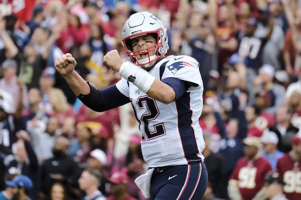 """FILE - In this Oct. 6, 2019, file photo, New England Patriots quarterback Tom Brady (12) reacts to a touchdown against the Washington Redskins during the second half of an NFL football game in Washington. Brady, the centerpiece of the New England Patriots' championship dynasty over the past two decades, appears poised to leave the only football home he has ever had. The 42-year-old six-time Super Bowl winner posted Tuesday, March 17, 2020, on social media """"my football journey will take place elsewhere."""" The comments were the first to indicate the most-decorated player in NFL history would leave New England. (AP Photo/Mark Tenally, File)"""