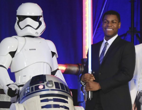 """FILE - In this Dec. 10, 2015 file photo, actor John Boyega, right, pose with Star Wars characters during the Japan Premiere of their latest film """"Star Wars: The Force Awakens"""" in Tokyo. Black actor John Boyega has stepped down from his role as a global ambassador for perfume brand Jo Malone, according to his Twitter announcement Tuesday Sept. 15, 2020, after the company decided to hire a Chinese actor to replace him in an ad he created. (AP Photo/Koji Sasahara, File)"""