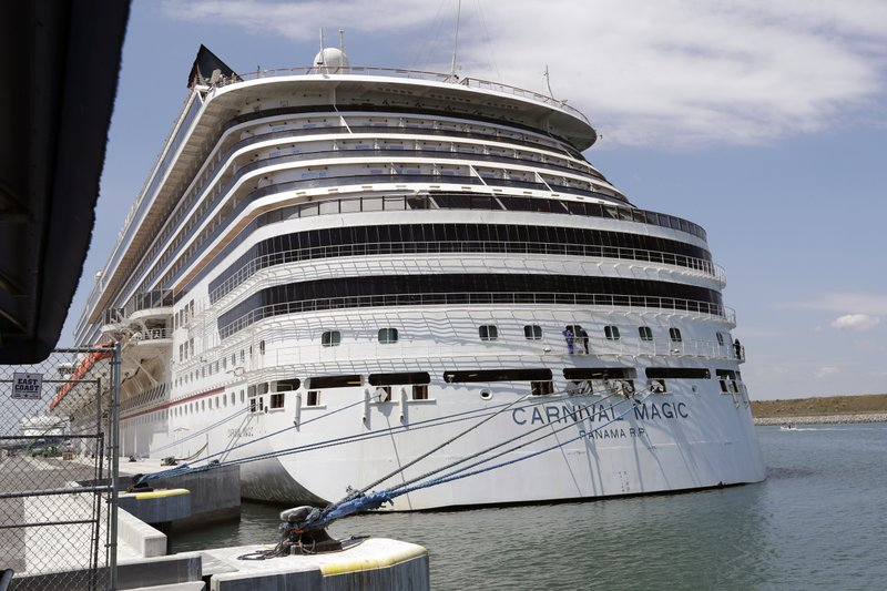 FILE - In this Saturday, April 4, 2020, file photo, Carnival cruise line ship Carnival Magic is docked at Port Canaveral, in Cape Canaveral, Fla. Carnival Cruise Line is canceling most U.S. sailings through the end of this year, the latest sign that the cruise industry's recovery from the coronavirus pandemic could still be many months away. The company said Thursday, Oct. 1, 2020, it is canceling sailings from all ports except its home ports of Miami and Port Canaveral, Florida. (AP Photo/John Raoux, File)