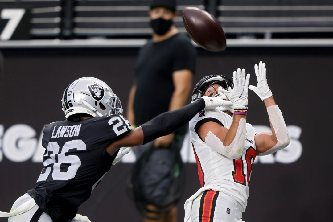 LAS VEGAS, NEVADA - OCTOBER 25: Scotty Miller #10 of the Tampa Bay Buccaneers catches a touchdown pass while being guarded by Nevin Lawson #26 of the Las Vegas Raiders in the second quarter at Allegiant Stadium on October 25, 2020 in Las Vegas, Nevada. (Photo by Jamie Squire/Getty Images)
