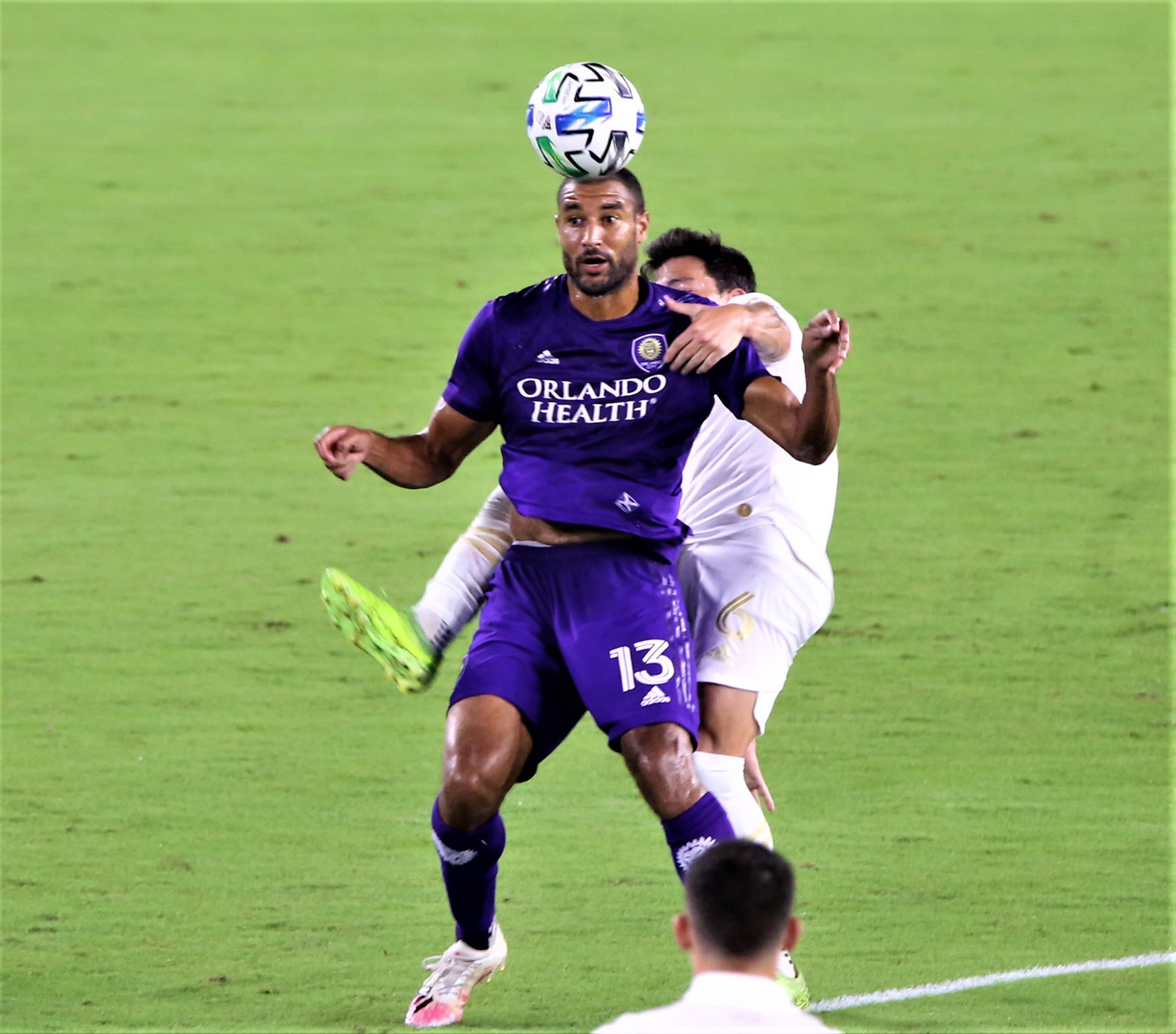 Orlando City SC's Tesho Akindele (#13) heads a flying pass in a typically physical against Atlanta United FC at Exploria Stadium Wednesday night. Photo: Willie David / Florida National News.
