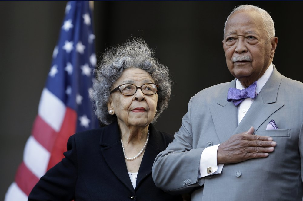 """FILE - In this Oct. 15, 2015, file photo, former New York City Mayor David Dinkins, right, and his wife, Joyce Dinkins, stand at attention as they listen to """"The Star-Spangled Banner,"""" during a ceremony renaming the Manhattan Municipal Building to the David N. Dinkins Building, in New York. Dinkins, New York City's first African-American mayor, died Monday, Nov. 23, 2020. He was 93. (AP Photo/Mary Altaffer, File)"""