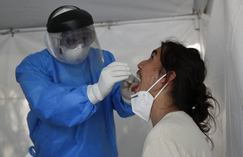 A healthcare worker collects a sample to test for the new coronavirus inside a mobile diagnostic tent, in the Coyoacan district of Mexico City, Friday, Nov. 13, 2020. Mexico City announced Friday it will order bars closed for two weeks after the number of people hospitalized for COVID-19 rose to levels not seen since August. (AP Photo/Eduardo Verdugo)