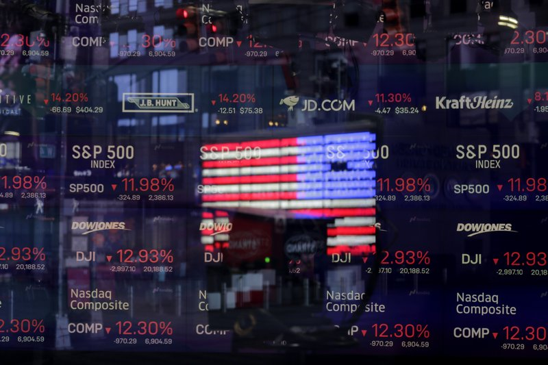 FILE - In this March 16, 2020 file photo, a United States flag is reflected in the window of the Nasdaq studio, which displays indices and stocks down, in Times Square, New York. Nasdaq is looking to become more diverse, proposing new rules that would require all companies listed on its U.S. exchange to publicly disclose consistent, transparent diversity statistics about their board of directors. The listing rules would also require most Nasdaq-listed companies to have, or explain why they don't have, at least two diverse directors. (AP Photo/Seth Wenig, File)