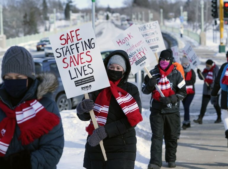 Nurses picket Friday, Feb. 12, 2021 in Faribault, Minn., during a healthcare worker protest of a shortage on protective masks. (AP Photo/Jim Mone)