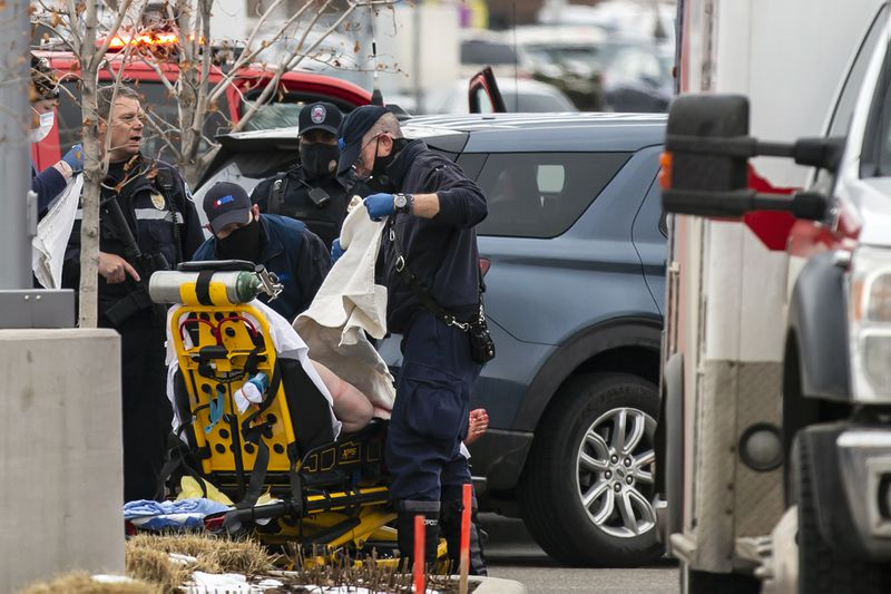 A man believed to be mass shooting suspect Ahmad Al Aliwi Alissa, who was escorted out of King Soopers in Boulder, Colorado in handcuffs after sustaining a gunshot to his right leg, is placed on a stretcher to be treated at a hospital Monday, March 22, 2021. Photo: Getty Images.
