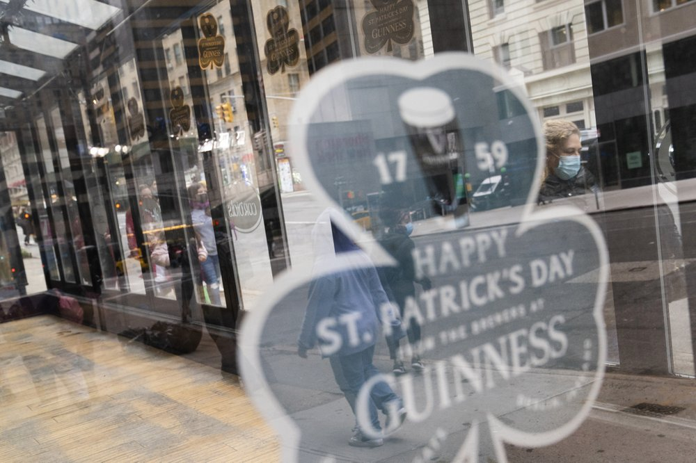 Pedestrians pass a shuttered dining area outside The Stagecoach Tavern on Saint Patrick's Day in midtown Manhattan, Wednesday, March 17, 2021, New York. (AP Photo/John Minchillo)