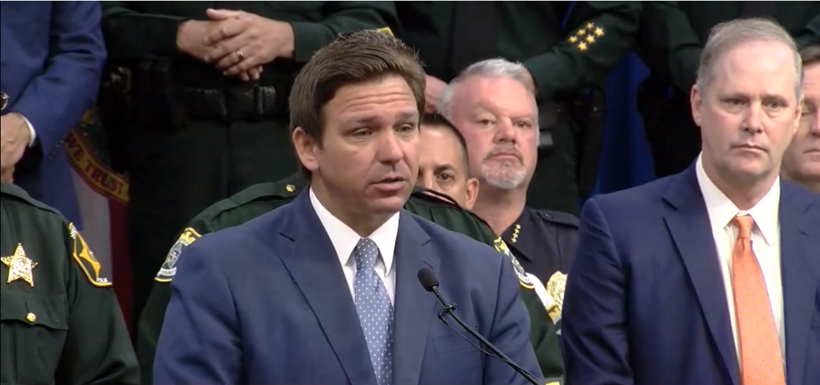 """FILE - Governor Ron DeSantis talks with press after signing HB 1, the """"anti-riot"""" bill, in Winter Haven, Florida Monday, April 19, 2021. File image: WFLA News Channel 8 (screen capture)."""
