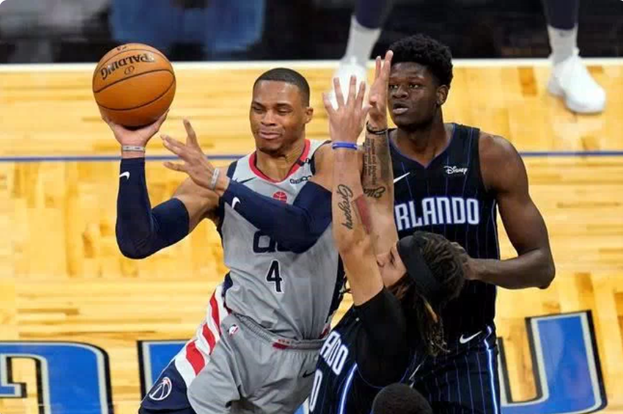 Washington Wizards' Russell Westbrook (#4) passes the ball against Orlando Magic's Mo Bamba (right) and Cole Anthony (foreground) at Amway Center Wednesday night. Photo via The Canadian Press.