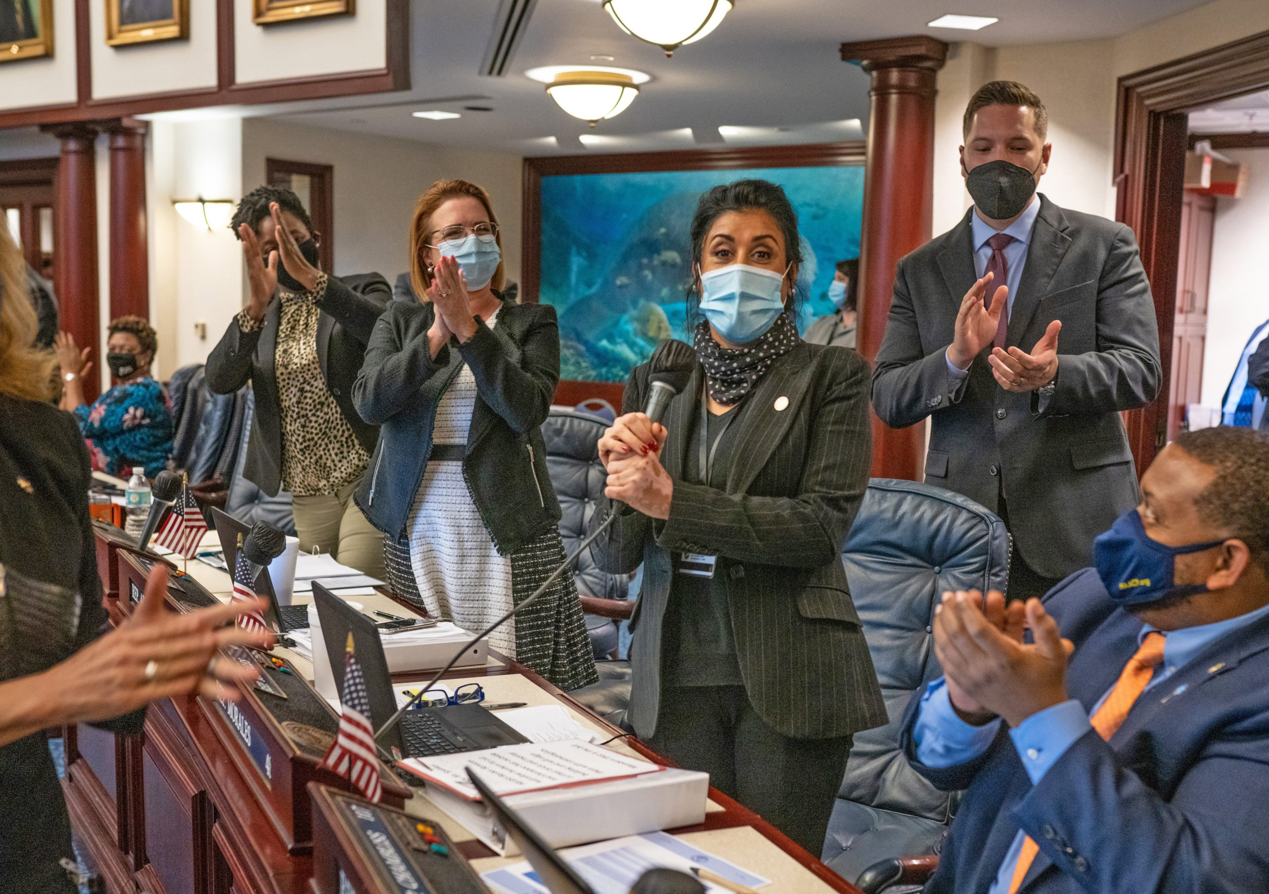 State Represntative Daisy Morales (center, holding microphone) garners bipartisan applause at the moment her Barber Services bill unanimously passes the Florida House. Photo: Florida House of Representatives.