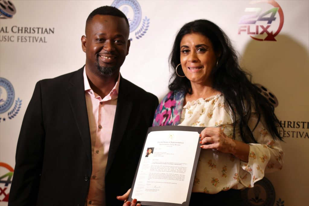 International Christian Film & Music Festival Founder Marty Jean-Louis (left) receives a welcome letter from State Representative Daisy Morales during the 2021 International Christian Film & Music Festival at the Wyndham Orlando Resort International Drive. Photo: Willie David/Florida National News.