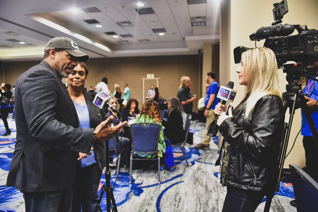 Actor/producer couple Cameron (left) and BJ Arnett (2nd from left) talk with Florida National News reporter Kathleen Michelle at the 2021 International Christian Film & Music Festival at the Wyndham Orlando Resort International Drive May 20, 2021. Photo: Harry Castiblanco/Florida National News.