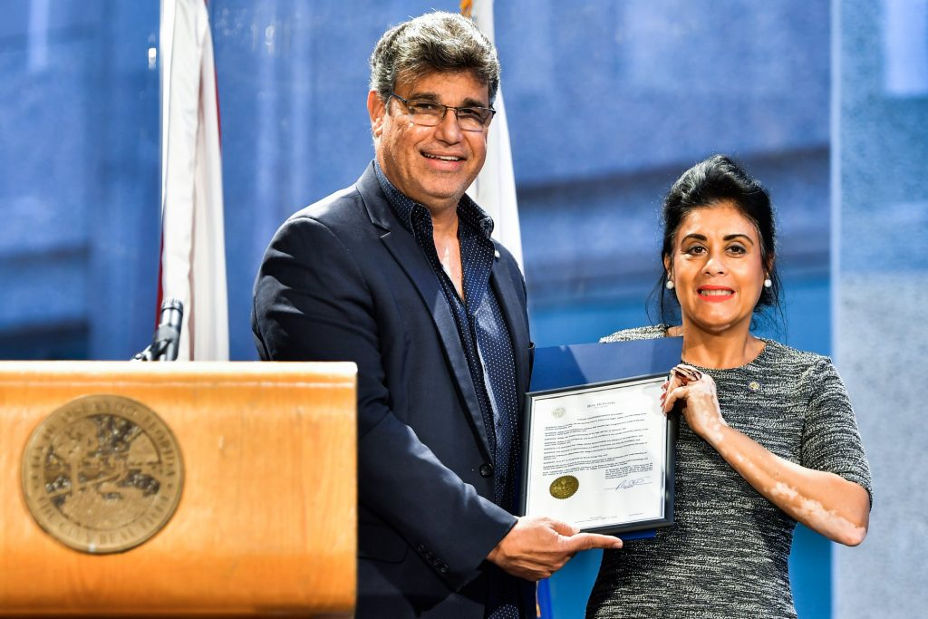 Orlando District 2 Commissioner Tony Ortiz (left) read Governor Ron DeSantis's proclamation recognizing June 25, 2021 as World Vitiligo Day and June 2021 as Vitiligo Month in the state of Florida during State Rep. Daisy Morales's (right) inaugural World Vitiligo Day event at Orlando City Hall Friday, June 25, 2021. Photo: Harry Castiblanco/Florida National News.