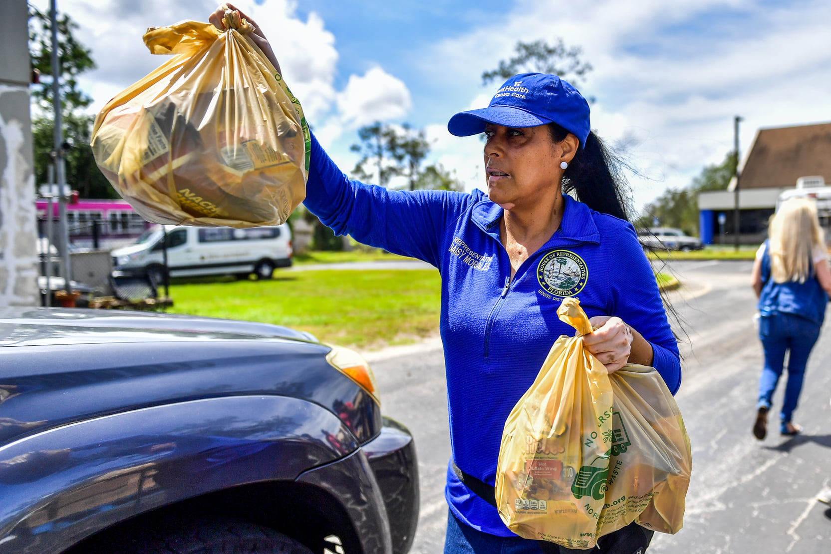 State Rep. Morales serves a driver with a bag of fresh produce during her free drive-up food distribution event at New Covenant Bible Fellowship Church in Orlando Satruday, June 5, 2021. Photo: Harry Castiblanco/Florida National News.
