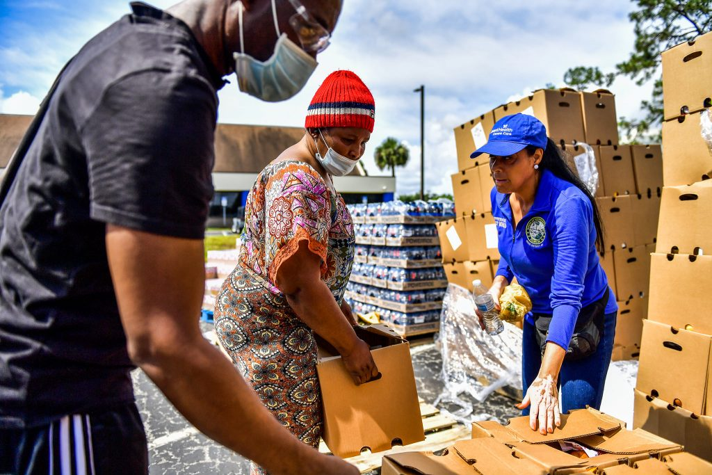 State Rep. Daisy Morales (right) helps a resident (center) gather food to take home for her family during her free food distribution event at New Covenant Bible Fellowship Church in Orlando Saturday, June 5, 2021. Photo: Harry Castiblanco/Florida National News.
