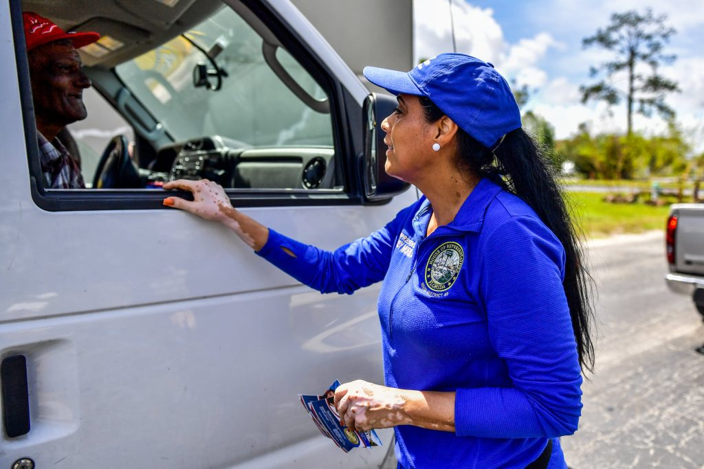 State Rep. Daisy Morales shares information with a resident as volunteers load his van with free food during her food distribution event at New Covenant Bible Fellowship Church in Orlando Saturday, June 5, 2021. Photo: Harry Castiblanco/Florida National News.