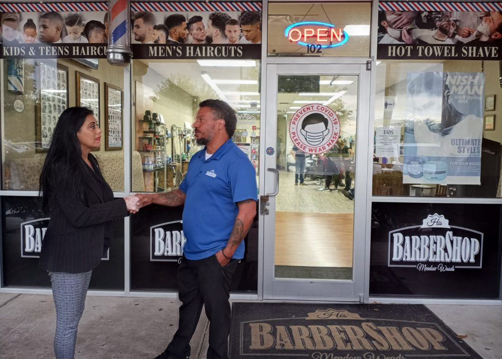 State Rep. Daisy Morales talks with Richard de la Rosa, owner of His Barbershop on Landstreet Rd. in Orlando. Photo: Mellissa Thomas/Florida National News.
