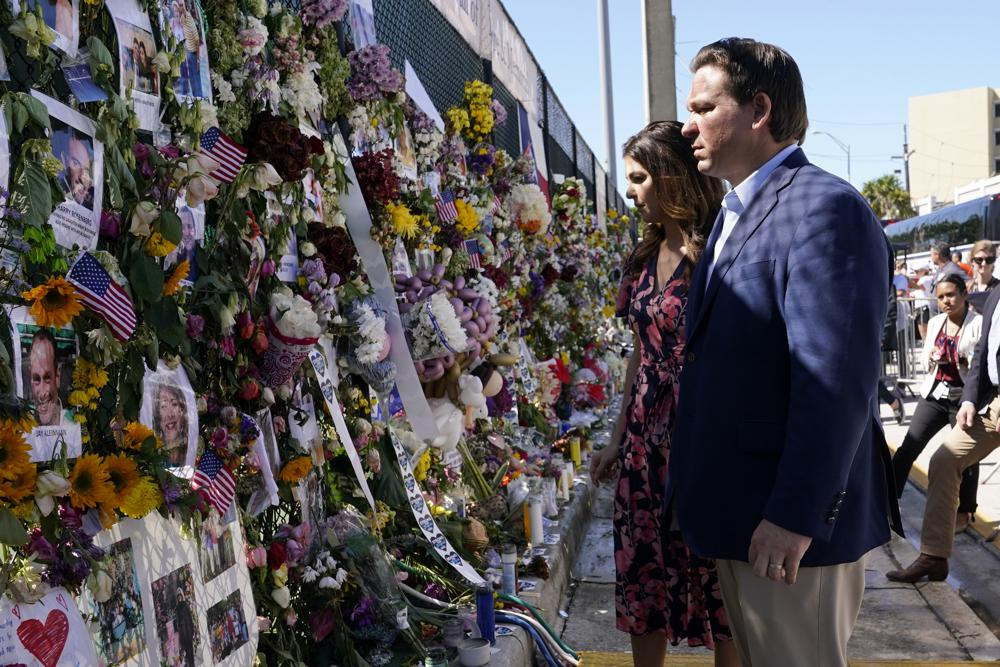 FILE - In this July 3, 2021, file photo Florida Gov. Ron DeSantis, right, and his wife Casey tour a makeshift memorial near the Champlain Towers South condo building, where scores of victims remain missing more than a week after it partially collapsed in Surfside, Fla. As he prepares for a reelection bid next year that could propel him into a presidential campaign, the tragedy in Surfside is exposing voters to a different side of DeSantis. (AP Photo/Lynne Sladky, File)