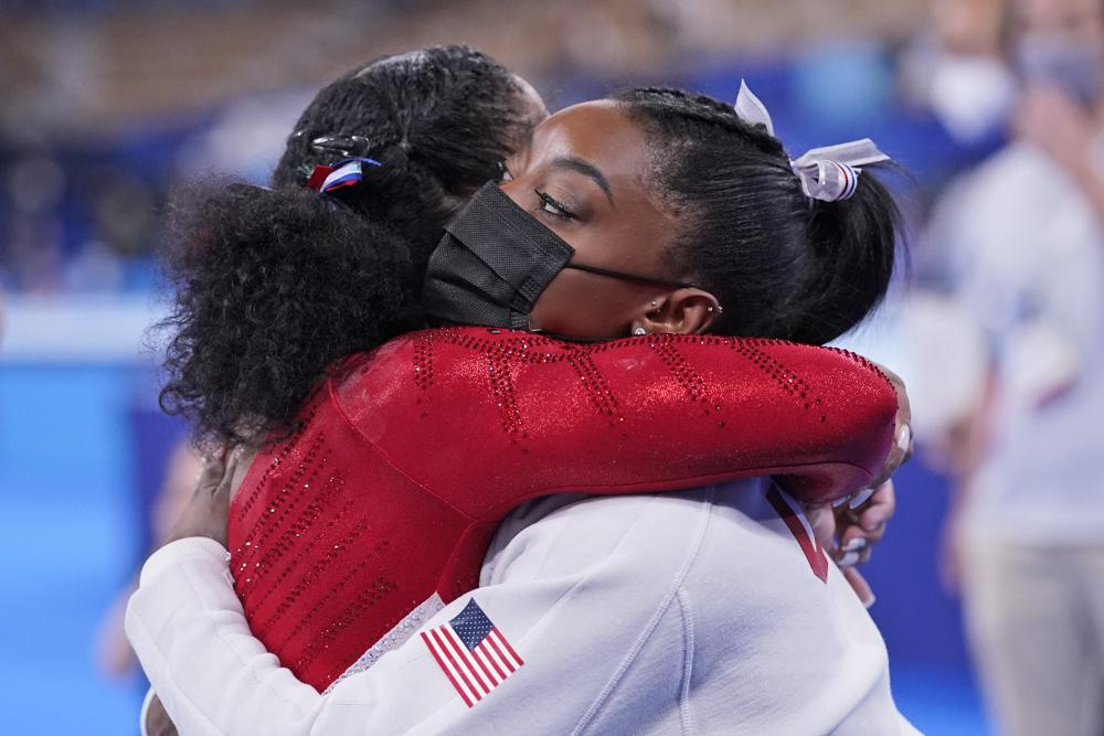 Simone Biles, of the United States, embraces teammate Jordan Chiles after she exited the team final with apparent injury, at the 2020 Summer Olympics, Tuesday, July 27, 2021, in Tokyo. The 24-year-old reigning Olympic gymnastics champion Biles huddled with a trainer after landing her vault. She then exited the competition floor with the team doctor. (AP Photo/Gregory Bull)