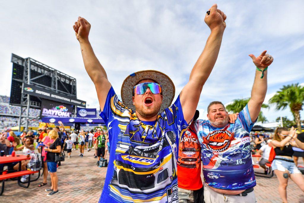Fans, wearing their favorite racers on their shirts, cheer during Chris Lane's Coke Zero Sugar 400 pre-race concert at Daytona International Speedway. Photo: Harry Castiblanco/Florida National News.