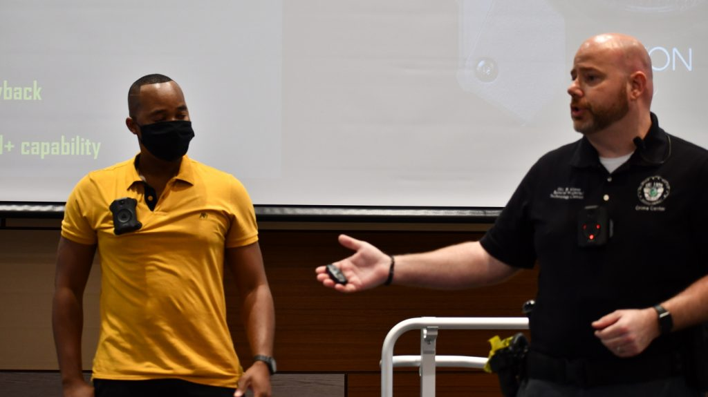 Orlando Police Officer Bradley Vilmer (right) demonstrates the new BWC on another police officer at OPD Headquarters in downtown Orlando. Photo: Juan Carlo Rodriguez/Florida National News.