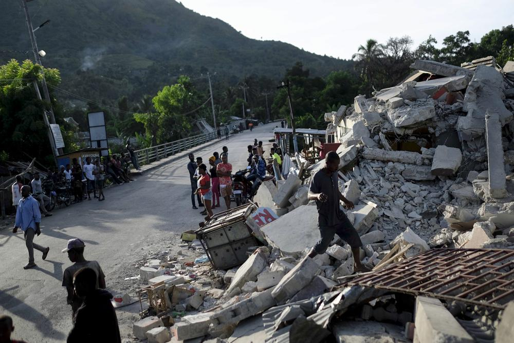 A man walks on a collapsed building in Saint-Louis-du-Sud, Haiti, Monday, Aug. 16, 2021, two days after a 7.2-magnitude earthquake struck the southwestern part of the hemisphere's poorest nation on Aug. 14.(AP Photo/Matias Delacroix)