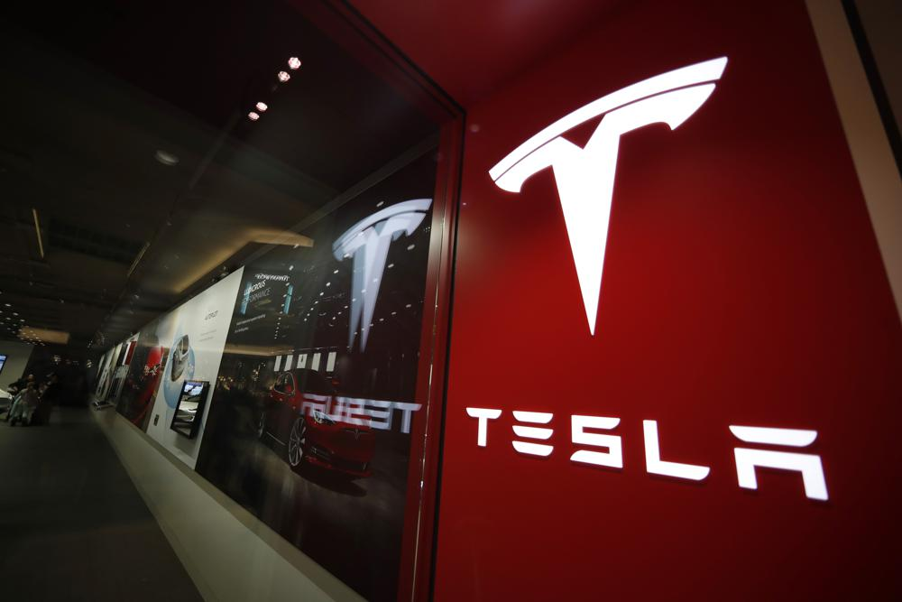 FILE - This Feb. 9, 2019, file photo shows a sign bearing the company logo outside a Tesla store in Cherry Creek Mall in Denver. A Tesla using its partially automated driving system slammed into a Florida Highway Patrol cruiser Saturday, Aug. 28, 2021 on an interstate near downtown Orlando and narrowly missed its driver, who had pulled over to assist a disabled vehicle. (AP Photo/David Zalubowski, File)