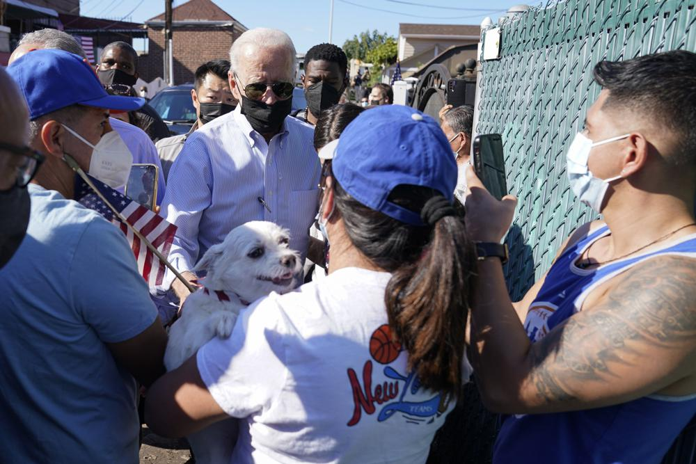 President Joe Biden talks with people as he tours a neighborhood impacted by flooding from the remnants of Hurricane Ida, Tuesday, Sept. 7, 2021, in the Queens borough of New York. (AP Photo/Evan Vucci)